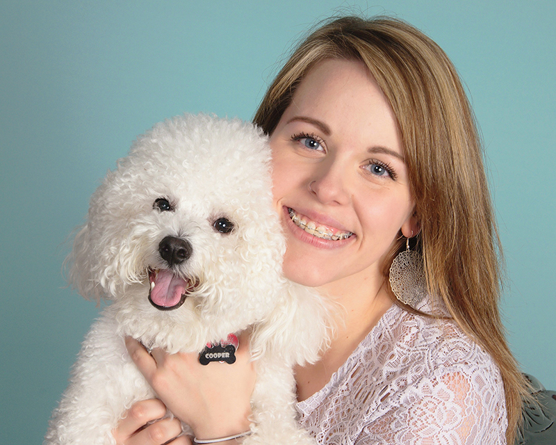 Girl with braces from Nelson R. Diers Orthodontics smiling and holding pet dog