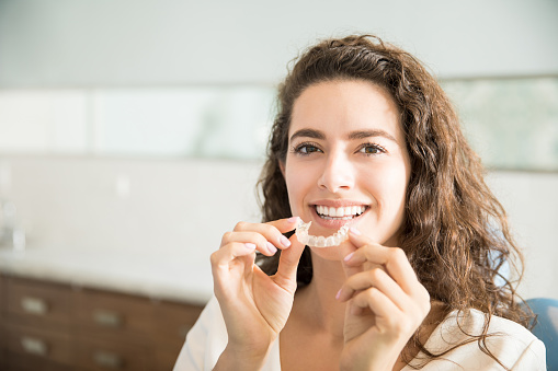 Woman trying on Invisalign aligners at Nelson R. Diers Orthodontics