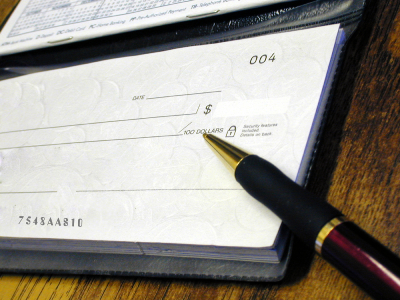 A check book with blank check and a pen at Nelson R. Diers Orthodontics